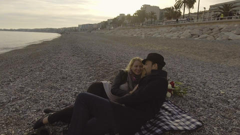 Young couple lying on beach and talking, woman kissing man, loving relationship Live Action