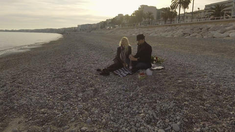 Man and woman in love having picnic by seaside, opening bottle of wine, date Live Action