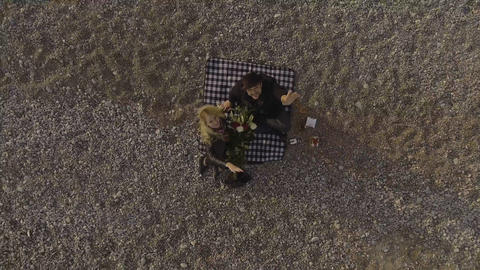 Woman and man sitting on blanket on beach, looking up and waving, aerial view Live Action