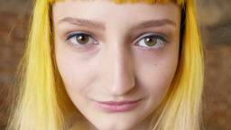 Close portrait of woman's face with yellow hair looking at camera and smiling Footage