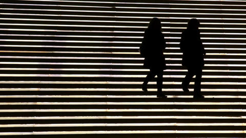Silhouette of five women in a staircase light Archivo