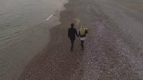 Dating couple walking on seashore holding hands, girl... Stock Video Footage