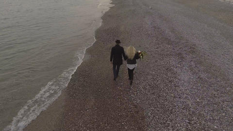 Dating couple walking on seashore holding hands, girl carrying flowers, date Live Action