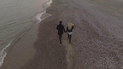Dating couple walking on seashore holding hands, girl…, Live Action