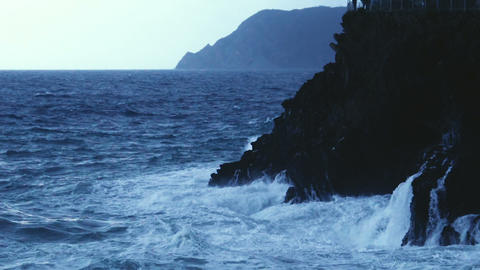 Dramatic powerful ocean waves splashing and breaking into rocky cliff, slow-mo Footage