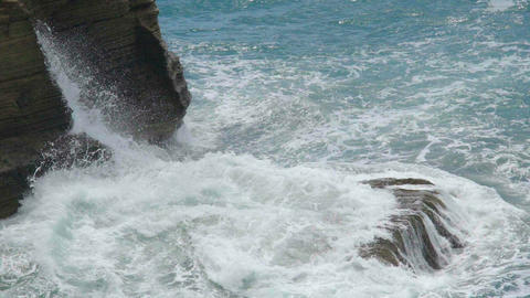 Sea waves breaking into splashes against rocky cliff creating foam by coastline Live-Action