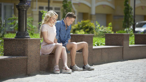 Male and female sitting on bench next to each other, feeling awkward, first date Live Action