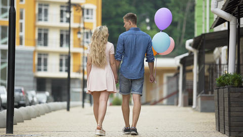 Couple walking down street holding hands, stopping to kiss, guy with balloons Footage
