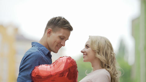 Happy couple approaching each other and kissing, hiding behind heart balloon Footage