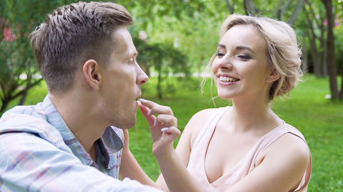 Flirty blonde feeding handsome young man with sweet raspberry, tender picnic Live Action
