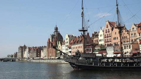 Stylized tourist sail ship turning on river, ancient historical houses on bank Footage