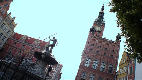 Fountain with Neptune statue in front of building with clock tower in Gdansk Footage