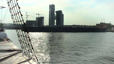 Sail boat approaching shipping platform, office buildings under construction Footage