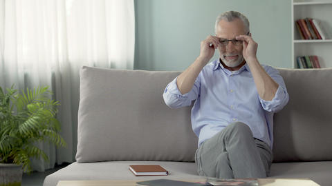 Healthy senior man sitting on sofa, wearing eyeglasses, dreaming about holiday Footage