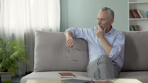 Optimistic senior male sitting on sofa and planning his vacation, retirement Footage