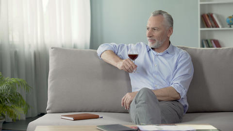 Thoughtful male in his fifties sitting on sofa and enjoying taste of red wine Footage