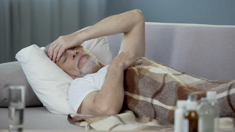 Old person sleeping in bed and suffering from terrible headache, illness Footage