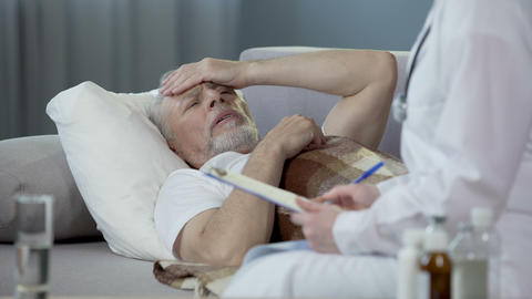 Senior man lying on sofa and talking with doctor about health problems. Disease Live Action