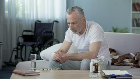 Senior handicapped male sitting on sofa and taking pills,... Stock Video Footage