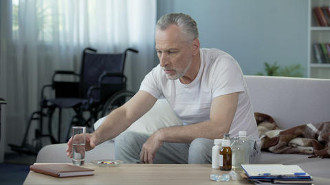 Senior handicapped male sitting on sofa and taking pills, loneliness and sadness Live Action
