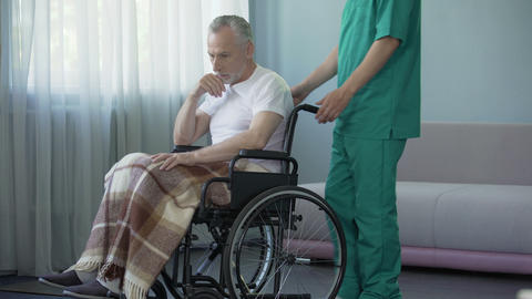 Lonely old man sitting in wheelchair at hospital, hopes to see relatives Footage