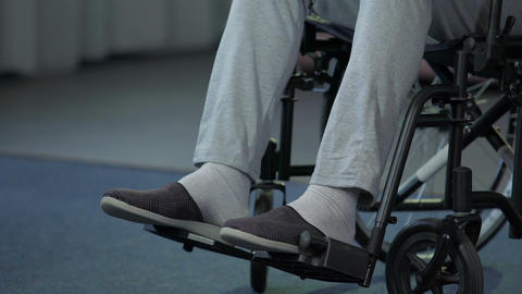Old male in wheelchair purposefully moving forward, hoping for quick recovery Footage