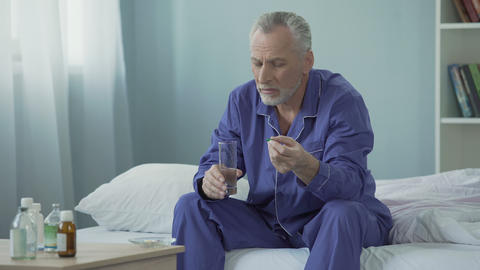 Senior man taking daily vitamin complex to maintain genitourinary system Live Action