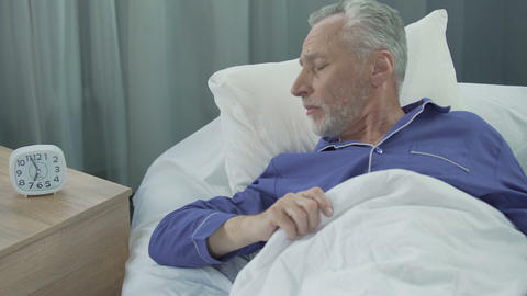 Man in his 60 waking up from loud ringing of alarm clock, time for work, morning Live Action