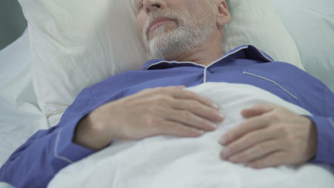 Senior man sleeping in bed and snoring loudly, problems with sleep, apnea Live Action