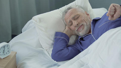 Senior man waking up active and full of energy after comfortable healthy sleep Footage