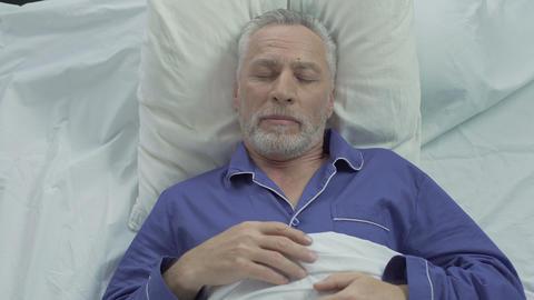 Senior man enjoying sleeping comfort due to orthopedic mattress and pillows Footage