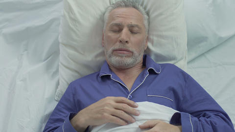 Senior man loudly snoring and puffing in bed, sleeping problems at old age Live Action