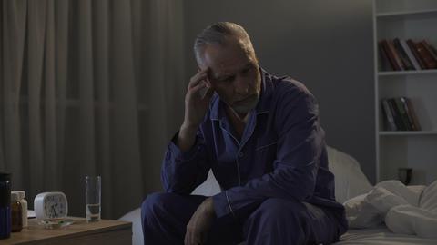 Sleepless senior man suffering from headache, taking painkillers at night Footage