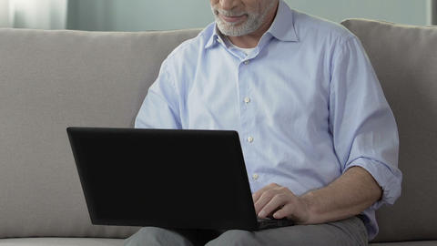 Aged man sitting on couch, using laptop, working from home, engineering project Footage