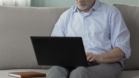 Grey-haired male using laptop, online communication, bride search online service Footage