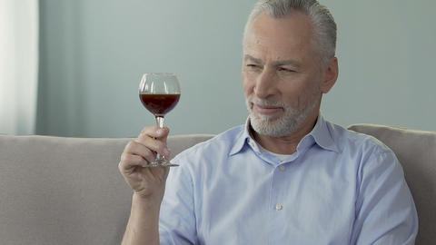 Grey-haired man sitting on couch and holding glass of wine, enjoying its smell Footage