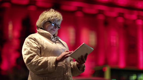 Senior woman with tablet PC stands near the road and red building in nighttime Footage
