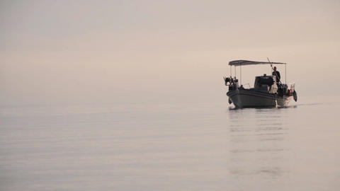 Motor boat fisherman, who returns from the sea with small waves wide after dawn  Footage