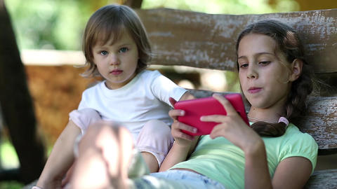Two little girls with red smartphone sits on swing bench Footage