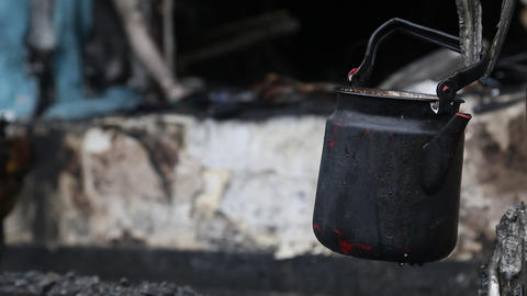 Black kettle on charred ruins in burnt building Footage