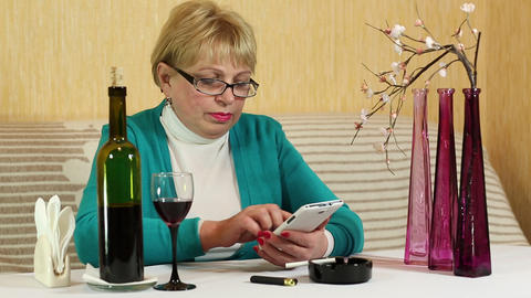 Woman sits at the table, drinks red wine and uses smartphone Footage