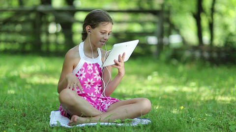 Beautiful girl with tablet computer sits on the grass in garden Footage