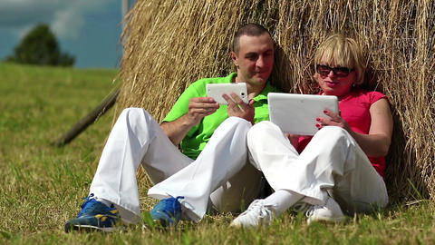 Man with white smartphone and woman with white tablet PC sits near a haystack Footage