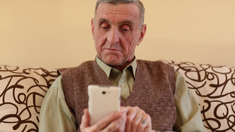 Senior man looks and flips through the photos in her smartphone Footage