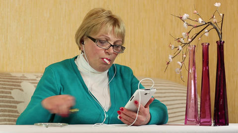 Woman in glasses with smartphone sits at a table and smokes a cigarette Footage