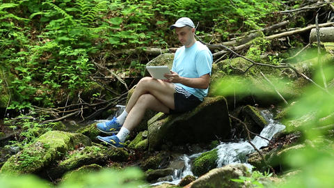 Man with tablet computer sits near small river in forest Footage
