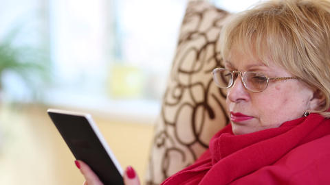 Senior woman sits on a sofa and reads electronic book. Woman reads a book Footage