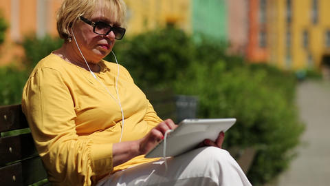 Woman in yellow jacket uses tablet computer. Woman holds Tablet-PC with earphone Footage