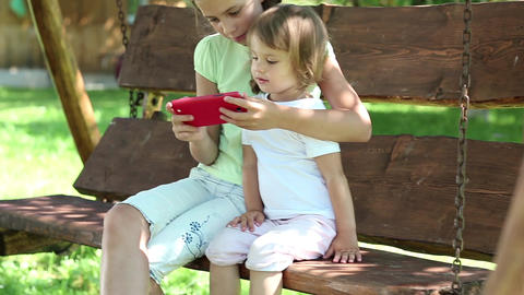 Two nice girls with red smartphone sits on the swing bench in garden Footage