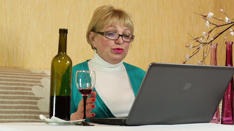 Woman with a bottle of wine sits at a table and communicates via laptop Footage